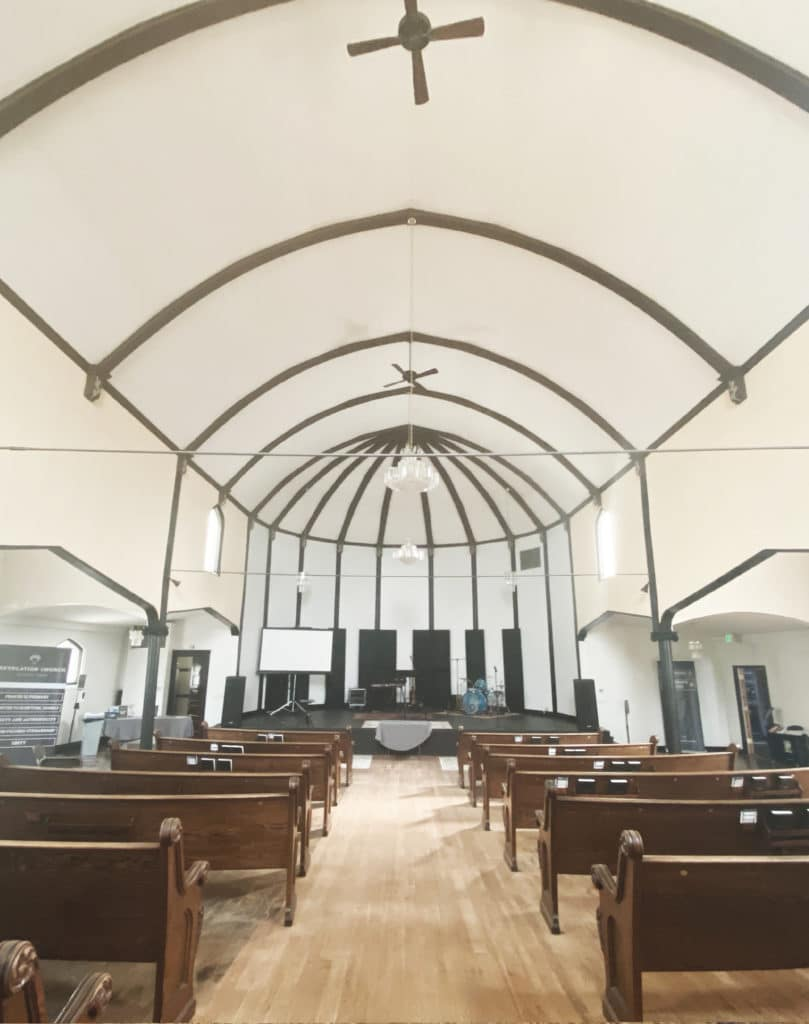View of Archwood Hall main auditorium space with pews and vaulted ceilings in CDA Idaho.